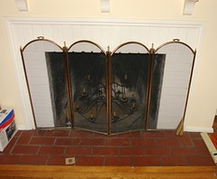Fireplace with metal screen and chandelier inside