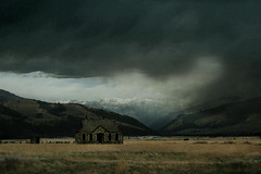 Landscape with Old Loneliness and Prairie Storm (MaureenShaughnessy) Tags: mountains history weather 1025fav dark spring montana solitude open seasons meadow 2550fav pasture utata romantic lonely prairie stories mountainrange toston bigskycountry elkhorns montanaranch stonecabin newwestnet outhereyoucanseeastormmovinginfromalongwaysoff andyoucanseeitmovinon ifyoudontliketheweatherinmontanastickaroundafewminutes