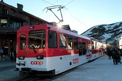 Panorama - Triebwagen Bhe 4/8 142 der Wengernalpbahn WAB mit Werbung COOP - Pro Montagna ( Baujahr 2004 - Zahnradbahn - Schmalspur 800 mm - Hersteller Stadler Rail AG ) am Bahnhof auf der Kleinen Scheidegg im Berner Oberland im Kanton Bern der Schweiz (chrchr_75) Tags: albumzzz201612dezember christoph hurni chriguhurni chrchr75 chriguhurnibluemailch dezember 2016 albumwabwengernalpbahn wab wengernalpbahn schmalspur schmalspurbahn bergbahn bahn train treno zug eisenbahn zahnradbahn schweizer bahnen albumbahnenderschweiz2016712 albumbahnenderschweiz schweiz suisse switzerland svizzera suissa swiss juna zoug trainen tog tren поезд lokomotive паровоз locomotora lok lokomotiv locomotief locomotiva locomotive railway rautatie chemin de fer ferrovia 鉄道 spoorweg железнодорожный centralstation ferroviaria zahnrad mountaintrain cogwheel crémaillère cremallera