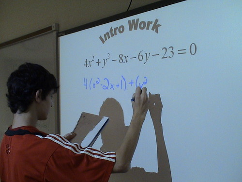 A student working an equation on a smart board.