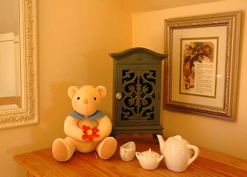 Staging for small north bedroom, with teddy bear, tea set and Alice in Wonderland quote. Creamy warm, friendy and familiar, with a little whimsy. by Wonderlane