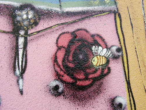 graffiti of a flower, a bee hovering over, maybe a microphone in the background?