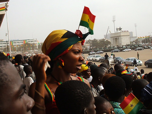 A Ghanaian woman, adorned in the colours of Ghana's national flag