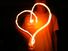 His Heart's on Fire. (The Vision Beautiful) Tags: light white love dark fire wolf long exposure shadows slow heart song flames tshirt parade burning flame shutter passion match lighter title firey