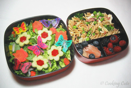 [left bento tier with decorated salad; right bento tier with pasta and fruit]