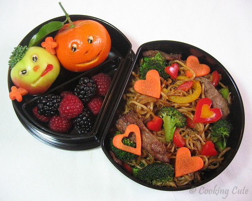 [half moon bento with carved fruit, berries, and yakisoba]