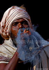 Smoking Sadhu (Raminder Pal Singh) Tags: street travel light people india man black strange face look out nose eyes asia hand view nikond70 expression cigarette smoke holy question come wrist through cloth smoker hinduism wristband baba hold sadhu saffron behold offbeat nostrils amaze headgear chillam fpg artlibre