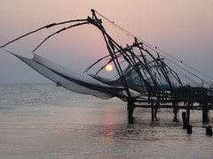 Sun caught up in Chinese Fishing Nets. (peggyhr) Tags: sunset sky sun india reflection water bravo oneofakind violet 123 kerala explore cochin soe shiningstar chinesefishingnets waterreflections aphoto naturesfinest supershot 50faves shieldofexcellence impressedbeauty aplusphoto onlyyourbestshots mybestpictureoftheweek blueribbonphotography superbmasterpiece 25faves123 lunarvillage globalvillage2post1giveaglobeto5 heartawards onlythebestare my10bestnaturephotosever 1on1sunrisesunsetsphotooftheweek 1on1sunrisesunsetsphotooftheweekseptember2007 simplysuperb explorewinnersoftheworld