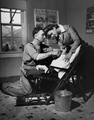 Dentist making an extraction (John Collier Jr.) Tags: blackandwhite bw usa history classic film museum america vintage collier us photographer unitedstates propaganda wwii documentary patriotic roosevelt historic professional worldwarii 1940s archives maxwell ww2 americana civildefense patriotism archival forties largeformat anthropology homefront worldwar2 40s fsa wartime newdeal owi waryears farmsecurityadministration officeofwarinformation johncollierjr