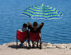 Enjoying the Sun (A Great Capture) Tags: red lake ontario canada water umbrella spring couple rocks chairs drink ashley ad backpack lakeontario oakville 2007 on ald canadianphotographer scoopt ashleyjeff torontophotographer ash2276 ash2275 ashleyduffus canadianphotogpraher ashleysphotography ald ashleysphotographycom ashleysphotoscom ashleylduffus wwwashleysphotoscom
