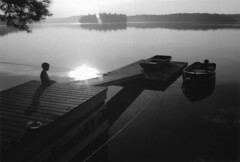 Morning on Beaver Lake (peterkelly) Tags: morning boy bw sun mist ontario canada reflection tree film water boats boat dock child shoreline canadian calm shore northamerica peterborough beaverlake