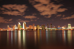 Downtown San Diego at Night (olasis) Tags: california city urban panorama reflection water skyline night clouds buildings lights bay downtown waterfront view nightshot bright sandiego pano panoramic growth development finest sandiegobay longexpsoure redevelopment americasfinestcity 5photosaday
