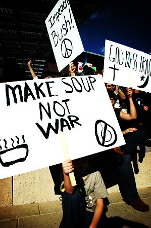 "Protestors hold up signs reading, ""Impeach Bush!,"" ""Make Soup Not War,"" and ""God Bless Iraq."""