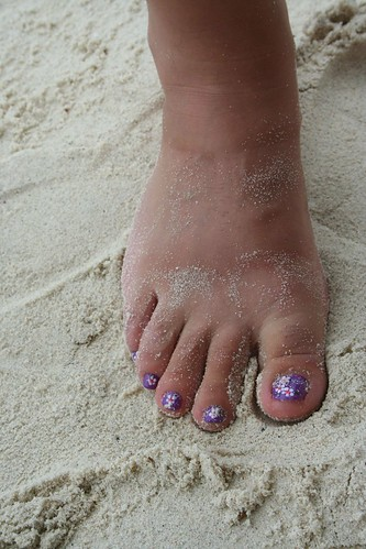 Toenails with hand painted ocean blue design with flower nail art