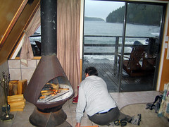 Tending the fire on a cold day (Ruth and Dave) Tags: wood dave fire cabin vancouverisland burning stove tofino duffincove