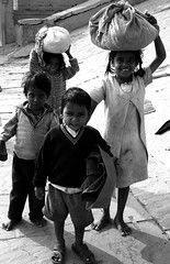 Little labors in Varanasi (Wen-Yan King) Tags: poverty india smile kids youth work children poor barefoot varanasi grin bags frown childlabor