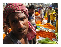 flower sellers | Kolkata (arnabchat) Tags: portrait orange india flower look yellow river market explore kolkata bengal calcutta howrahbridge arnabchat arnabchatterjee