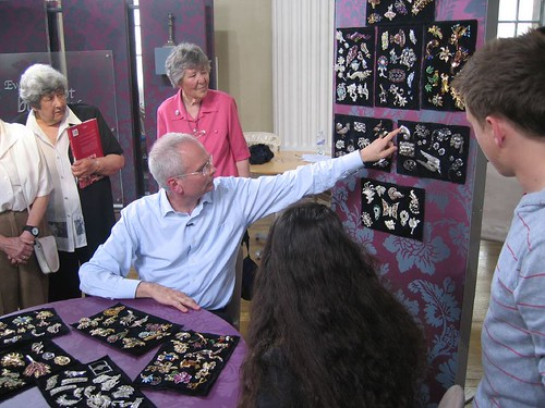 Expert Geoffrey Munn pointing at one of the brooches
