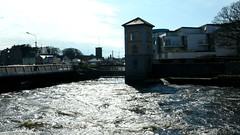 Fishery Watch Tower on the River Corrib, Galway City. (RuthannOC) Tags: county old city bridge blue ireland sky irish white black west mill galway church water sunshine stone swimming buildings river way flow outdoors lumix canal duck stream corrib arch cathedral lock path walk dam ripple bridges wave bank sunny eire quay panasonic spanish eglinton western strong locks ripples paths flowing archway mills current dams ruthann woodquay dmcfz50