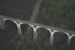 Malnate - A bridge (_ Night Flier _) Tags: above travel sky italy panorama tree green nature forest airplane landscape flying high view earth top aviation aerial fromabove lombardia varese cessna skyview lombardy birdeye aeronautic malnate