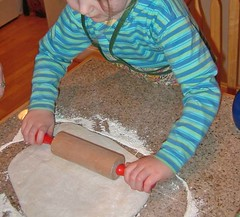 awesomeGrrl rolling out pizza crust
