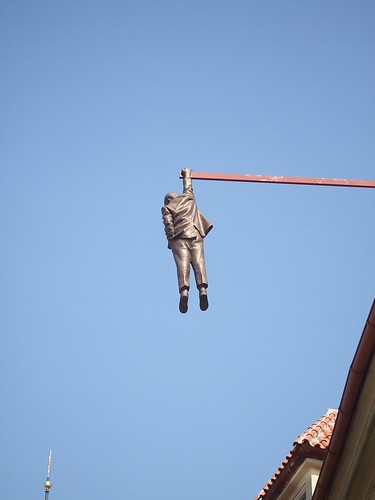A bronze statue hanging from one of the buildings representing the fall of communism.