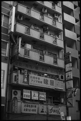 Ads and Living (gullevek) Tags: blackandwhite building film sign japan architecture writing ads poster geotagged tokyo books   ilford  housebuilding  scannedfromnegative olympusom2n iso125 ilfordfp4125 epsongtx900 publictelefone zuikomc50mmf12 geo:lat=35687819 geo:lon=139699268