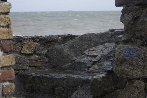 VIEW OF THE SEA THROUGH GAP IN BROKEN WALL