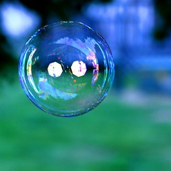 A soap bubble, caught in mid-air reflecting a photographer's flash