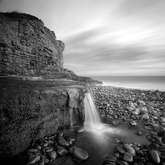 Monknash I (Adam Clutterbuck) Tags: ocean uk longexposure greatbritain sea blackandwhite bw seascape beach monochrome wales square landscape mono coast blackwhite waterfall rocks stream bn coastal shore elements glamorgan gb limestone bandw sq oe greengage monknash heritagecoast adamclutterbuck sqbw bwsq showinrecentset walglamheri openedition