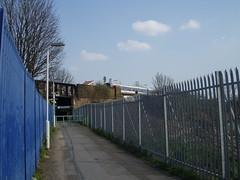 Footpath approach to South Bermondsey station, with train (Kake .) Tags: blue london train railway bermondsey footpath railings southlondon se16 southbermondsey