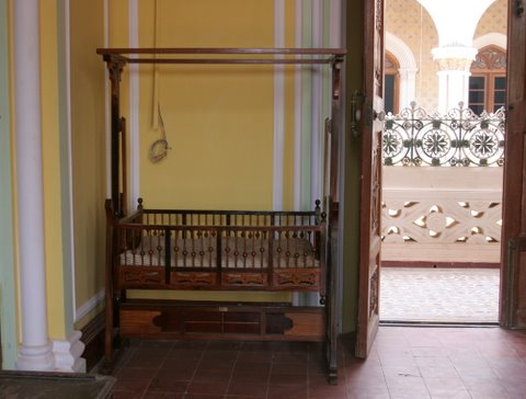 Bangalore Palace Chld's Cradle...and horrible wiring on the wall behind. Notice the filigree quality of the wrought iron railing seen through the  door