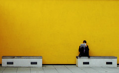 Reading His Paper (Bobshaw) Tags: man yellow wall bench paper newcastle reading newspaper candid seat minimal
