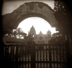 Carmel Mission (happygrrl) Tags: california usa west 120 film church sepia architecture holga gate toycamera ishootfilm spanish squareformat carmel gateway mission westcoast carmelmission ilford carmelbythesea beachtown carmelmissionbasilica secretpeeks spanishcoloniesintheunitedstates