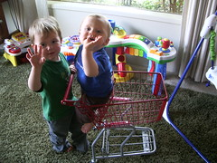3/30/07 Judah pushing Samuel in the shopping cart & waving