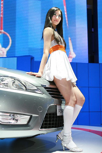 Asian model in white mini skirt near silver car