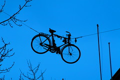 Bikes In Strange Places (Lady Vervaine) Tags: above street city blue sky urban cinema film strange up bike bicycle movie iceland funny turquoise object surreal reykjavik cycle hanging suspended et hang extraterrestrial bizzare suspend laugarvegur