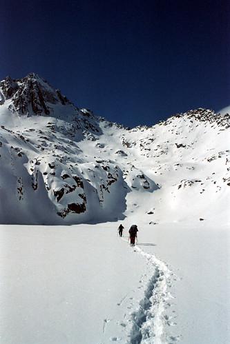 Grup d'excursionistes creuant un llac gelat