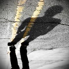 Penumbra (Austin Tolin) Tags: road street shadow urban lines silhouette yellow paint upsidedown squareformat figure mysterious cracks asphalt penumbra