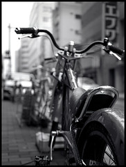 Kanda #17 (mechanics) Tags: city urban blackandwhite bw white black bike bicycle wheel japan tokyo 645 asia dof bokeh bronica  nippon medium  kanda ilford f4 nihon kanto mechanics rf chiyodaku shallowdepthoffield urbanlife  shallowdepth chiyoda 65mm    rf645  selfdevelop zenzanon