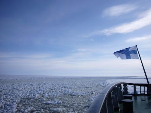Bandera de Finlandia ondeando al viento, enfrente de unos icebergs