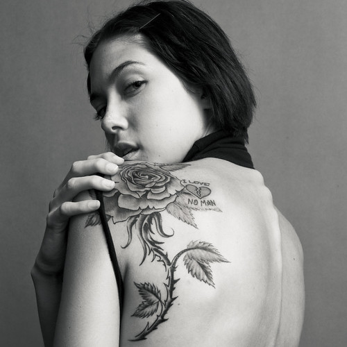 Picture of a girl with a rose tattoo on her upper back