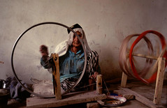 Spinning silk (BoazImages) Tags: china portrait woman face 1025fav work photo women desert silk xinjiang silkroad uyghur itsongselection1 mirrorsofsociety ethnic blueribbonwinner itsongnikonf601 itsongmirrorsmiddleeast womanworking