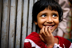 smiling red dress (phitar) Tags: unicef portrait 2004 girl smile wow eyes hand teeth topv1111 topc50 interestingness1 dhaka bangladesh topf200 galleria reddress theface phitar