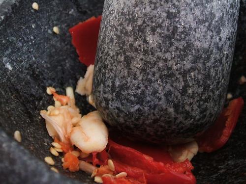 pestle and mortar crushing garlic and chillies
