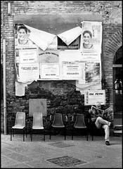 Reading. (flevia) Tags: bw italy reading chair italia 5 bn sit sangimignano toscana sedie ilford fp4 biancoenero giovani canonat1 bnvitadistrada bncitt bnpersone tamron28mmf28 flevia sagradellastiaccia