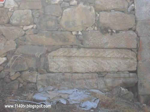 pedra pré-histórica na posição horizontal, com o desnho de uma folha de palmeira