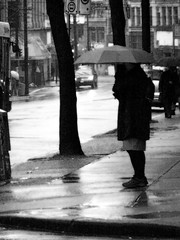 Hunched Under An Umbrella (victoria potter) Tags: city blackandwhite woman rain vancouver standing umbrella waiting downtown bc britishcolumbia voyeur peoplewatching hunched westhastings