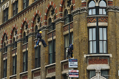 Window cleaners on Gothic building in London, EC1