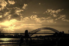 The 'Coathanger' Bridge (... Arjun) Tags: bridge sunset bw 15fav panorama water monochrome silhouette sepia clouds 1025fav 510fav bay nikon d70s overpass australia panoramic viaduct 2550fav 500v50f join nsw 50100fav link newsouthwales coathanger hook passage toned peg suspensionbridge tinted hanger channel connection conduit sydneyharbour association railwaybridge 2007 sydneyharbourbridge australasia thebridge bennelongpoint 75thanniversary thecoathanger 18200mmf3556g bluelist onlythebestare sydneycentralbusinessdistrict 335108s1511238e thewidestlongspanbridgeintheworld thelargeststeelarchbridge